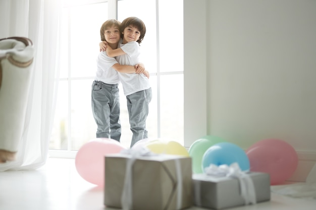 Due simpatici gemelli latini, bambini piccoli in abbigliamento casual che si abbracciano, sembrano felici, in piedi nella stanza con palloncini colorati e scatole regalo. vacanze, regali, concetto di infanzia