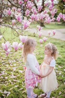 Due bambine bionde carine di 3 anni stanno giocando nel parco vicino a una magnolia in fiore. bere il tè. pasqua. primavera.