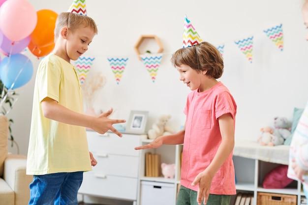 Due simpatici ragazzini in berretti di compleanno e magliette che giocano a giochi infantili a casa nella stanza decorata alla festa