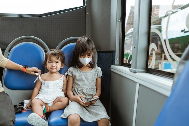 Due bambine carine sedute su una panchina con in mano un cellulare sull'autobus durante il viaggio