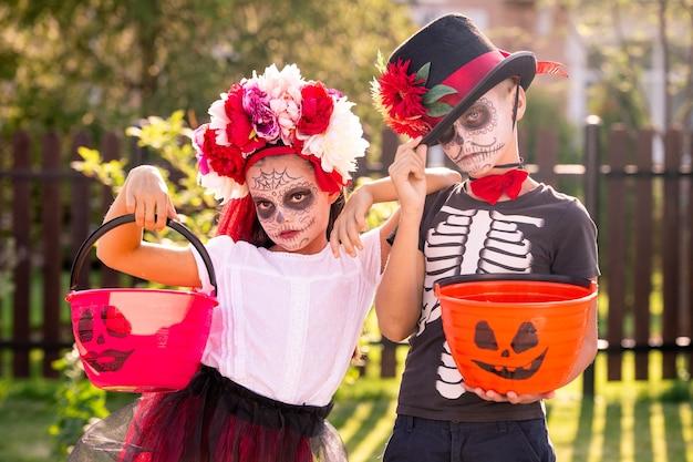 Due simpatici bambini di halloween con facce dipinte che tengono secchi con dolci mentre stanno uno vicino all'altro davanti alla telecamera