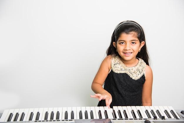 Due simpatiche ragazze indiane o asiatiche che suonano il pianoforte o la tastiera, uno strumento musicale, su sfondo bianco