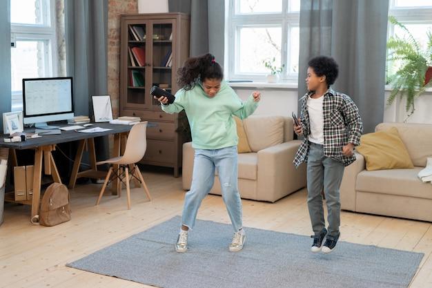 Due simpatici fratelli di razza mista in abbigliamento casual che si divertono sul pavimento mentre ballano e saltano sul tappeto grigio al centro del soggiorno
