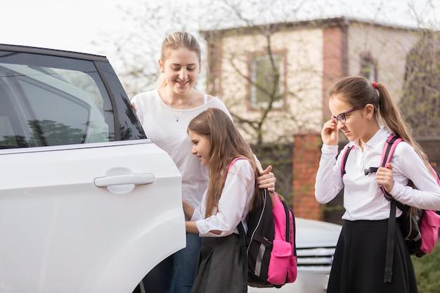 Due studentesse carine salgono in macchina per andare a scuola