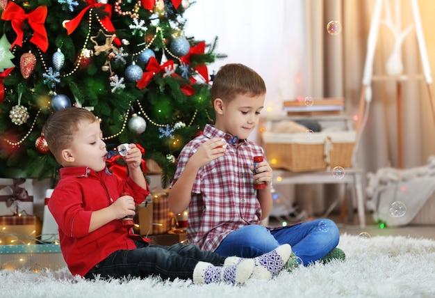 Due simpatici piccoli fratelli soffia bolle di sapone su sfondo albero di natale