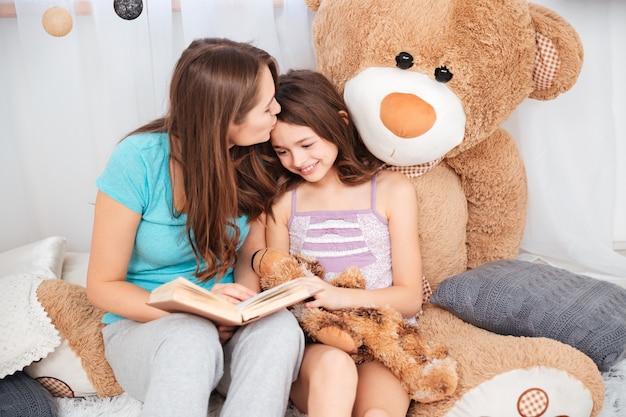 Due sorelle sorridenti carine che leggono e si baciano nella stanza dei bambini children