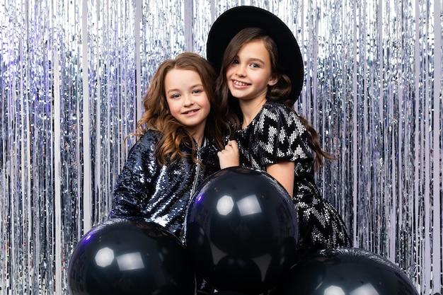 Due ragazze alla moda carine in abiti con palloncini neri