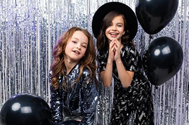 Due ragazze carine alla moda in abiti da festa con palloncini neri su una parete lucida