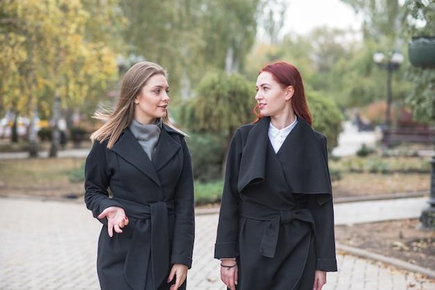 Due ragazze carine stanno camminando e parlando di argomenti importanti