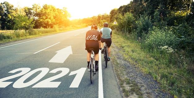 Due ciclisti stanno passando direttamente all'anno 2021