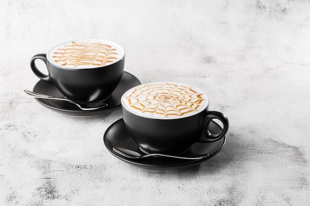 Due tazze di caffè scure con struttura di arte del latte del caramello del latte isolata su fondo di marmo luminoso. vista dall'alto, copia spazio. pubblicità per menu bar. menu della caffetteria. foto orizzontale.