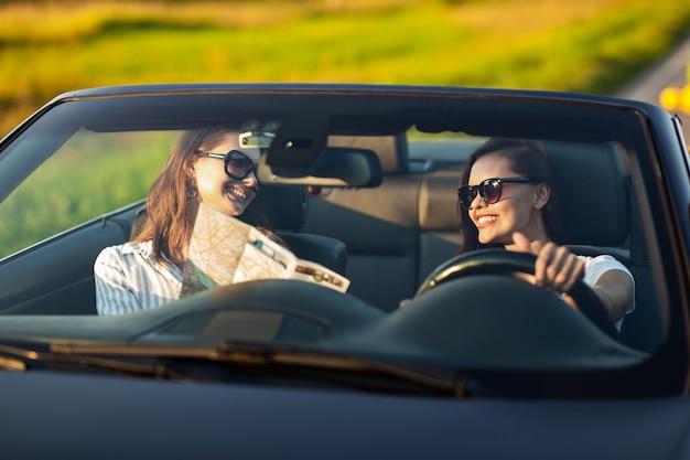 Due giovani donne dai capelli scuri in occhiali da sole sono sedute in un'auto decappottabile nera e sorridono in una giornata di sole. uno di loro tiene la mappa nelle sue mani. .