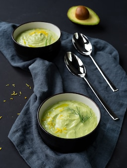 Due piatti scuri con crema di zuppa di cetrioli e avocado con scorza di limone e olio d'oliva su sfondo nero. vista dall'alto. orientamento verticale.