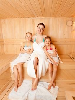 Due figlie con la madre seduta su una panchina in sauna