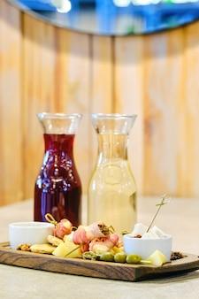 Due decanter con vino e piatto con snack