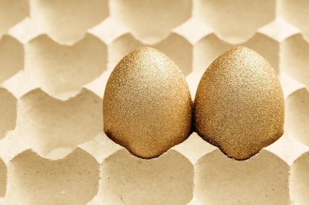 Due uova di pasqua decorate d'oro nel vassoio delle uova di cartone
