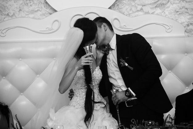 Due bicchieri decorati con uno champagne nelle mani della sposa e dello sposo ritratto in bianco e nero