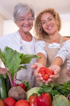 Due donne sfocate nella casa della cucina che tengono nelle mani piccoli pomodori rossi. crudo fresco raccolto in tavola