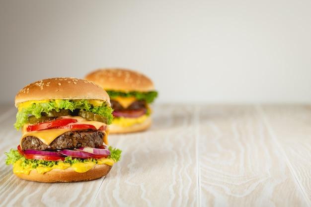 Due deliziosi hamburger con carne, formaggio fuso, salsa gocciolante e verdure su fondo rustico in legno bianco con spazio per il testo. gustosi hamburger appena fatti, primo piano e spazio di copia