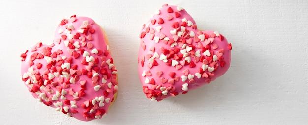 Due deliziose ciambelle a forma di cuore sul tavolo di legno