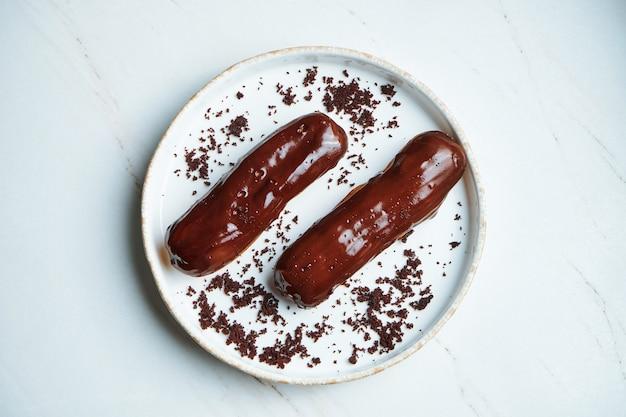 Due deliziosi bignè con crema pasticcera e glassa di cioccolato lucida su un piatto di ceramica bianca su una superficie di marmo. dessert e pasticcini appetitosi. vista dall'alto, orizzontale