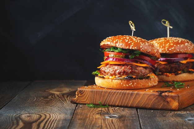 Due deliziosi hamburger fatti in casa di manzo, formaggio e verdure su un vecchio tavolo di legno. primo piano di cibo malsano..