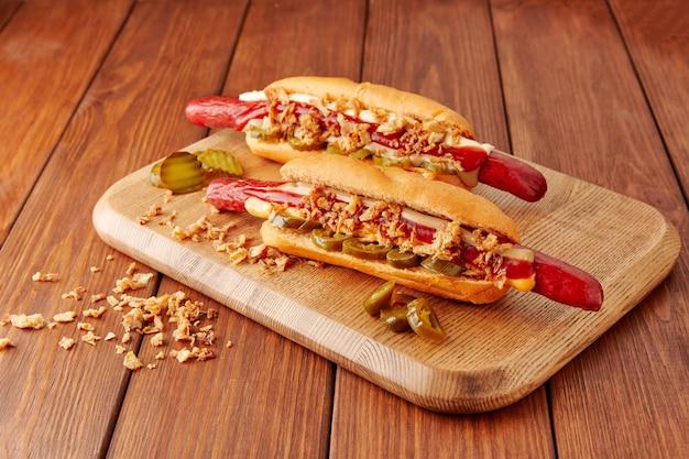 Due deliziosi hot dog si trovano su una tavola di legno su un tavolo di legno