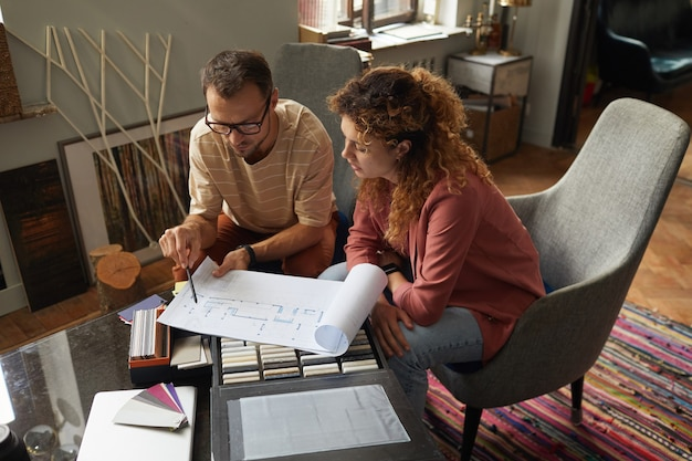 Due designer seduti al tavolo ed esaminando il progetto del nuovo progetto stanno lavorando in un ufficio moderno
