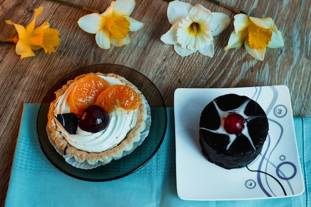Due dolci, uno al cioccolato con ciliegie, l'altro alla crema bianca con prugne e mandarini