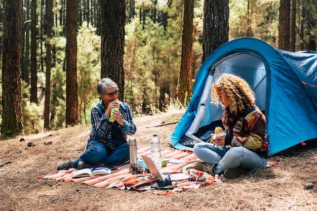 Due diverse età caucasica donna in campeggio libero insieme nella foresta di pini mangiando un panino