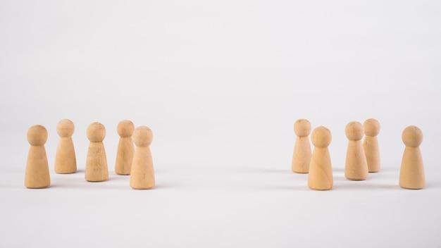 Due diversi gruppi di persone in piedi l'uno di fronte all'altro per l'uguaglianza e la concorrenza nel concetto di business.