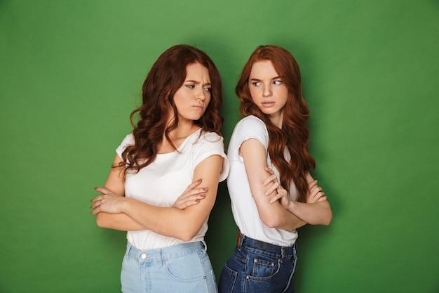 Due ragazze 20s scontenti con i capelli rossi in abbigliamento casual in piedi schiena contro schiena con le braccia incrociate e lo sguardo arrabbiato a vicenda, isolato su sfondo verde