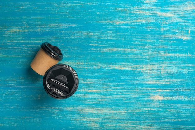 Due bicchieri di carta usa e getta di diverse dimensioni di caffè su una superficie di legno blu
