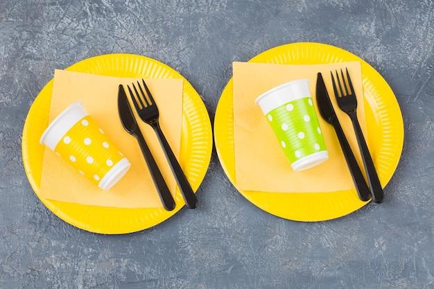 Due piatti usa e getta, forchette, bicchieri usa e getta e un tovagliolo