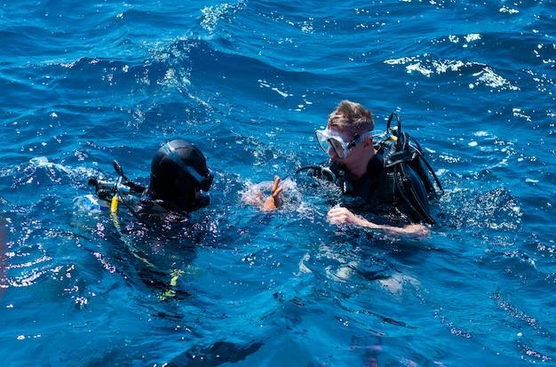 Due subacquei gesticolano in superficie