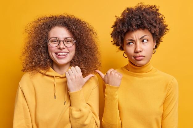 Due diverse donne amichevoli puntano i pollici l'una contro l'altra vestite con disinvoltura esprimono felicità e insoddisfazione isolate sul muro giallo. guarda il mio amico. amiche di razza mista indoor