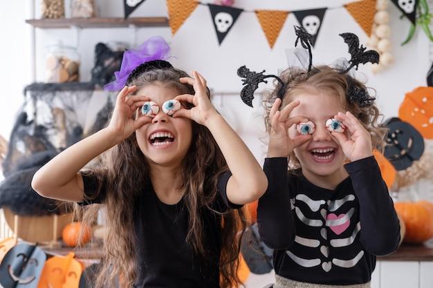 Due ragazze diverse in costume da strega, che si divertono a casa in cucina, festeggiano halloween.