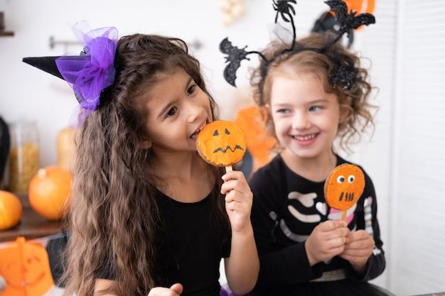 Due ragazze diverse in costume da strega, si divertono in cucina, mangiano biscotti, festeggiano halloween.