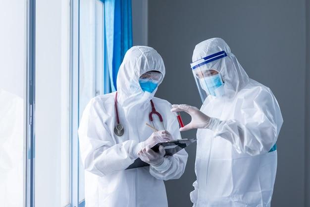 Due medici che tengono la provetta del campione di sangue su fondo bianco. concetto di epidemia di coronavirus o covid-19, concetto di trovare modi per prevenire la diffusione del coronavirus.