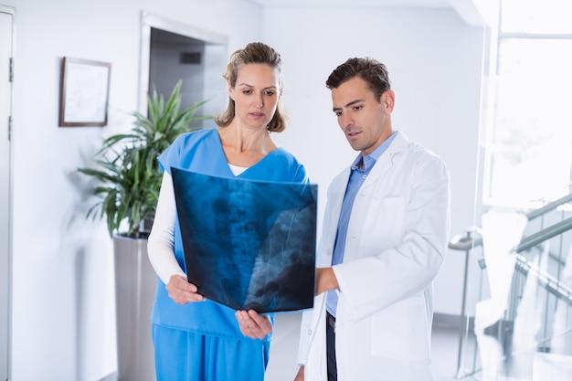 Due medici che esaminano i raggi x dei pazienti in corridoio