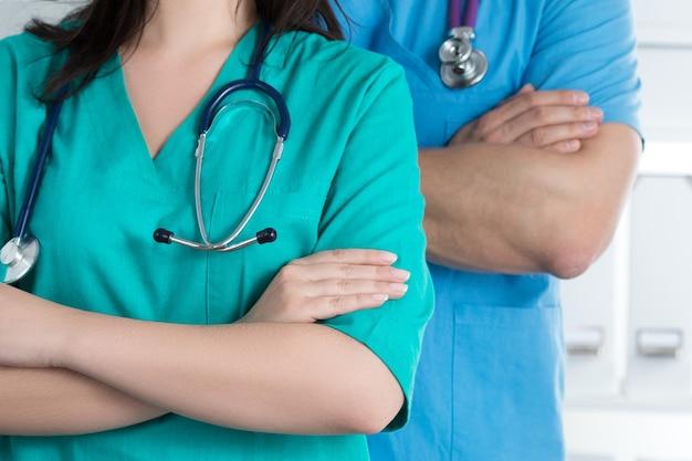 Due medici stanno in piedi con le braccia incrociate sul petto pronti a lavorare. sanità e concetto medico.