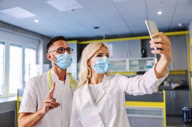Due medici in piedi in ospedale in una pausa e utilizzando i telefoni cellulari.