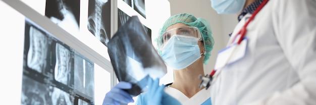 Due medici che indossano maschere protettive stanno esaminando i raggi x