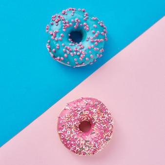 Due ciambelle su rosa pastello e blu. composizione di cibo creativo minimalismo. stile piatto laico