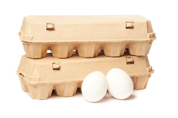 Due contenitori per uova isolati su sfondo bianco
