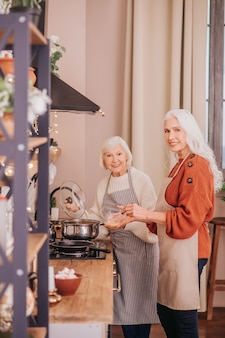 Due donne anziane in piedi in cucina