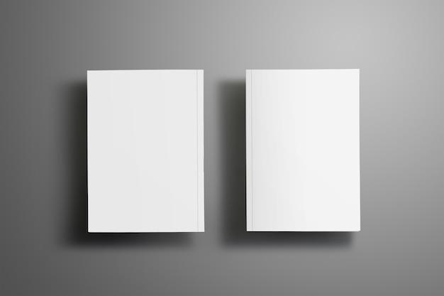 Due eleganti opuscoli chiusi in bianco a4, (a5) con morbide ombre realistiche isolate su superficie grigia. uno degli opuscoli è girato.