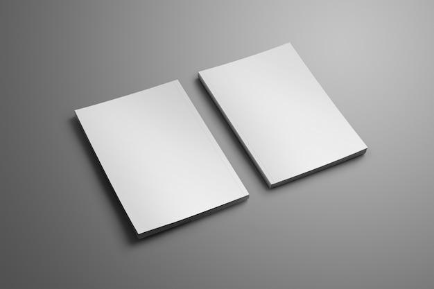 Due eleganti opuscoli chiusi in bianco a4, (a5) con morbide ombre realistiche isolate su superficie grigia.