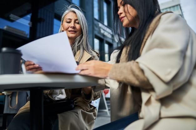 Due eleganti donne d'affari che studiano documenti in un caffè all'aperto
