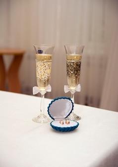Due eleganti bicchieri di vino bianco e fedi nuziali in una scatola sul tavolo